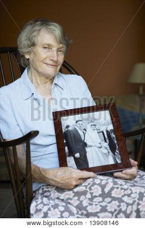 Senior Woman At Home Looking At Old Wedding Photo