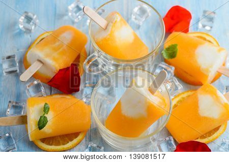 Homemade frozen ice cream popsicles made with oragnic fresh oranges on wooden background
