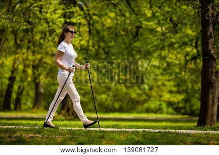 Nordic walking - middle-aged woman working out in city park