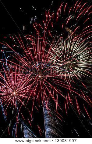 3 firework bursts together overhead, showering colors.