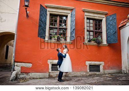 Wedding Couple Near Orange House With Windows