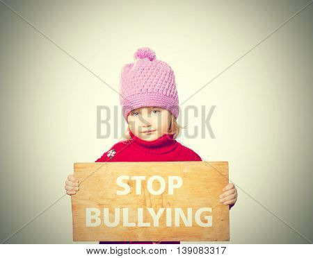 Little Girl Holding Board With Text Stop Bullying.