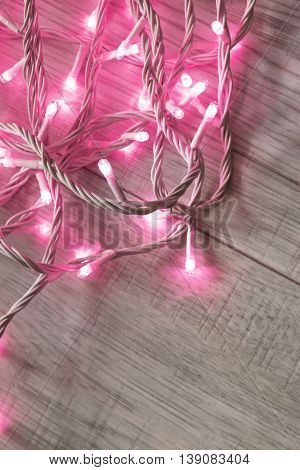 Pink flash lights on gray wooden floor as a background