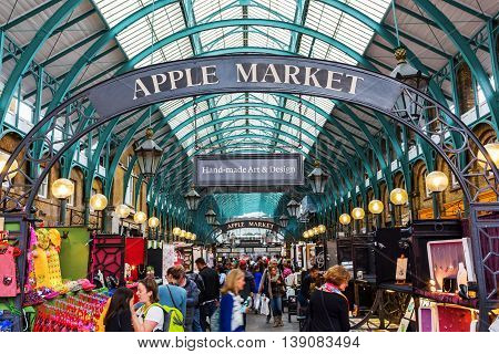 London UK - June 16 2016: Apple market in the market hall at Covent Garden with unidentified people. The historic hall is today a tourist location containing cafes pubs shops and two markets