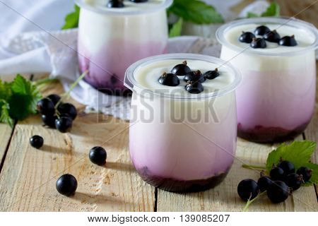 Homemade Yoghurt With A Black Currant On The Table In A Rustic Style.