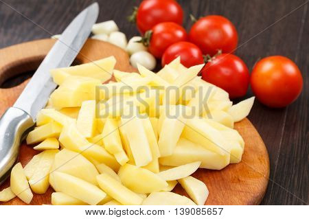 Cutting potatoes on a board chef cooking