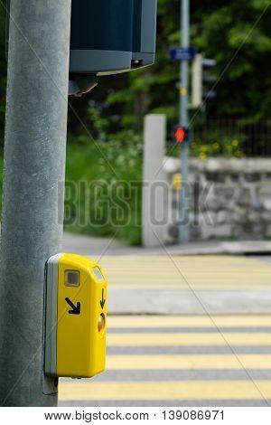 Yellow button at crosswalk for pedestrian traffic light aid in Geneva Switzerland