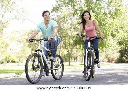 Young Couple Riding Bike In Park