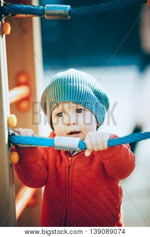 The boy in the cap standing on the Playground and held hands on the rope a bright Sunny day.