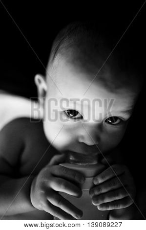 The baby looks into the camera with a bottle in hand sucking the juice from a baby bottle. Little boy. black and white image