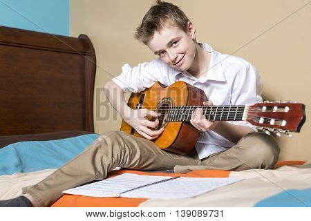 A teenage boy playing guitar in her bedroom