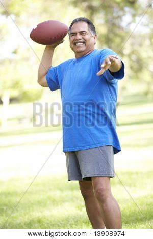 Senior Man Exercising With American Football In Park