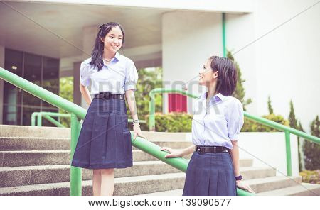 Cute Asian Thai high schoolgirls student couple in school uniform stand on the stairway making eye contact in vintage childhood color