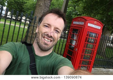 Tourist selfie with London phone box - red telephone kiosk in the UK.