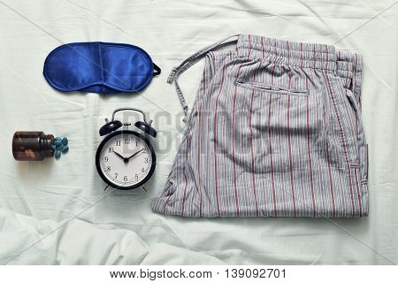 high-angle shot of a sleep mask, a bottle of sleeping pills, an alarm clock and a pajamas on a bed covered with a white bedsheet