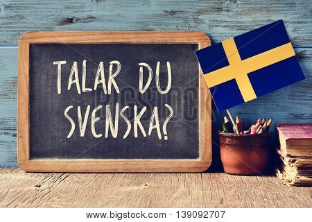 a chalkboard with the question talar du svenska?, do you speak Swedish? written in Swedish, a pot with pencils, some books and the flag of Sweden, on a wooden desk