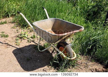 Building - the vintage thrown wheelbarrow in a high green grass.