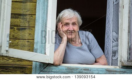 Retired grandmother sitting in the window of a village house.