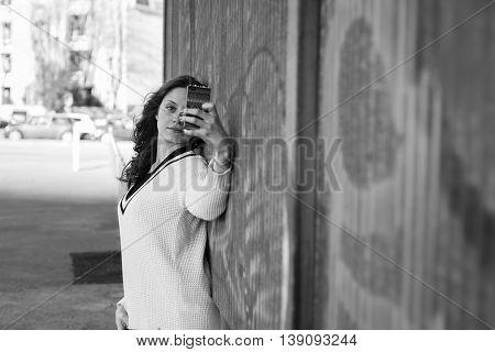 Gorgeous young woman with long hair taking a selfie in an urban context
