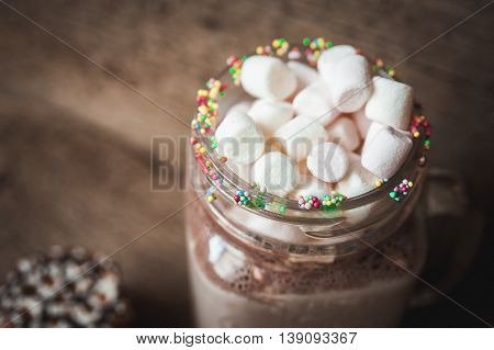 Cookies in chocolate and a bottle of cocoa with marshmallows. Wooden background