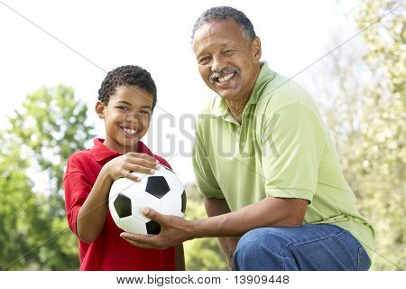 Grandfather With Grandson In Park With Football