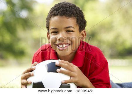 Junge im Park mit Fußball