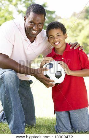 Vater und Sohn im Park mit Fußball