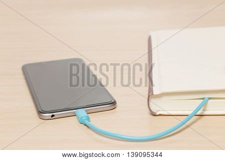 Smart phone connected to the old book with a cable and download information from there