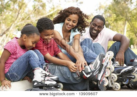 Family Putting On In Line Skates In Park