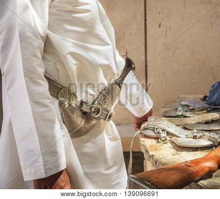 Man wearing khanjar - traditional Omani dagger on a belt at the gun market in Nizwa, Oman
