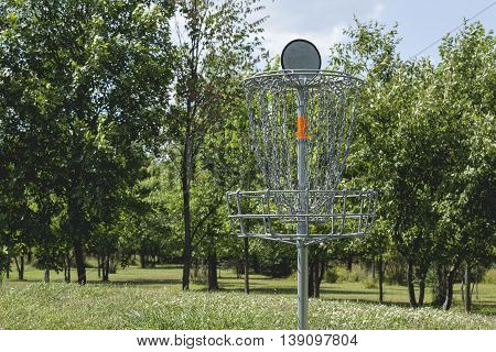 Golf basket on a course in front of trees