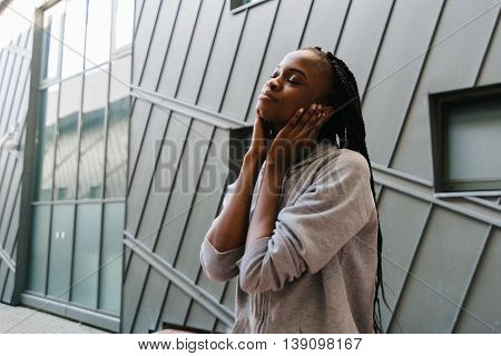 Young african american woman enjoying music with headphones and closed eyes.