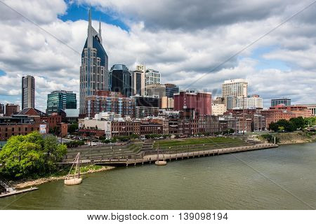NASHVILLE, TN - JUNE 5: A view of downtown Nashville on a summer day. This view is from a pedestrian bridge that crosses the Cumberland River.