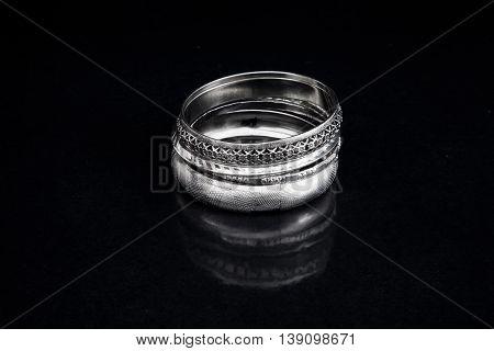 Silver bracelets with reflection on black base