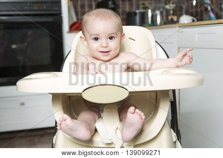 A portrait of a happy baby in the highchair kitchen