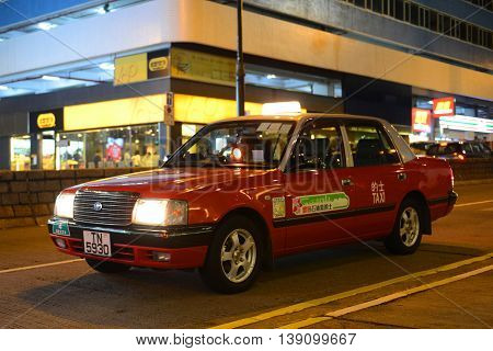HONG KONG - NOV 9: Hong Kong Urban red Toyota Crown Confort YXS10 four seats taxi at night on Nov 9, 2015 in Kowloon, Hong Kong.