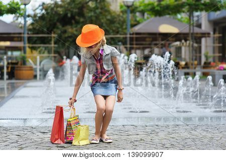 Elegant Charming cute little girl in fashionable clothes and sunglasses orange hat with full shopping bags. fountain in the background. shopping bags on the pavement.
