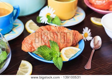 Tea Set And A Croissant On The Wooden Background