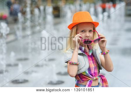 Portrait of girl in fashionable clothes. Elegant Charming cute little girl in sunglasses orange hat. Fountain in background. Little girl corrects sunglasses. Wear glasses.