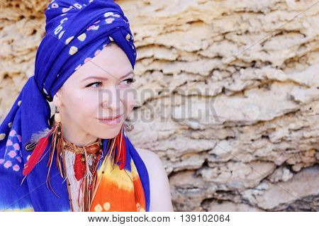 Young woman wearing boho chic scarf on a head and handmade feathers necklace and earrings, outdoor horizontal photo with space for text against stone