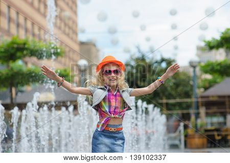 Pretty Little Girl Raised Her Hands Up. Portrait of girl in fashionable clothes. Elegant Charming cute little girl in sunglasses orange hat. Fountain in background.
