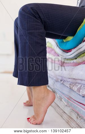 Tired woman in blue trousers sitting on the pile of mattresses relaxing after the working day. Bare feet of a girl.