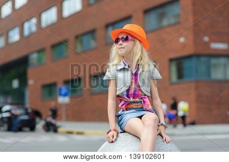 Portrait of girl in fashionable clothes. Elegant Charming cute little girl in sunglasses orange hat.