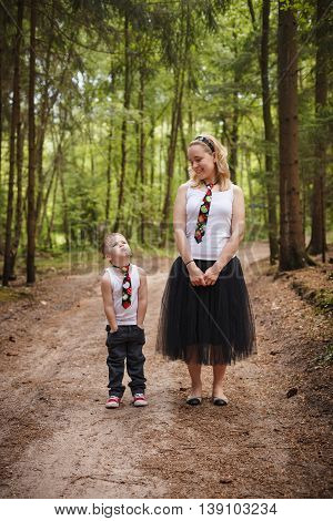 Young mother in a fluffy black skirt and a tie with her 4 years old son in back jeans white t-shirt and a tie in s summer forest. Stylish family look. Together walking in a countryside park