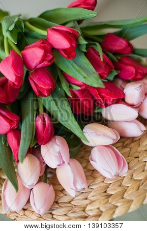 Beautiful bouquet of spring tulips flowers on the table. Red and pink tulips laying on the straw table mat.