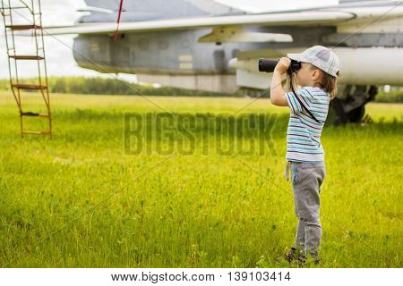 Boy looks through binoculars at the airfield