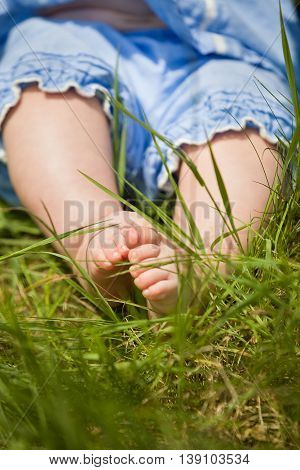 Feet of a small baby on the green grass. Sunny day. Cute child sitting on the ground. Barefoot of a infant.