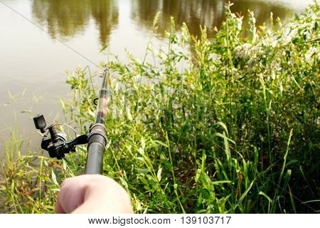 hand holding a fishing rod close. a man fishes on the lake