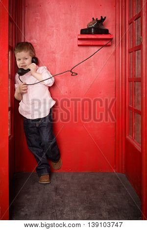 Cute little blond boy in a pink shirt and jeans call on the retro telephone in a British telephone box. Boy with an old telephone in the red phone booth in English style. Child with a black handset.