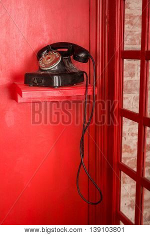 Red Telephone booth in English style. British phone box with black retro telephone standing in it. Vintage looking Red telephone box.